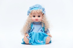 Beautiful baby doll with blond hair in blue dress isolated on white background
