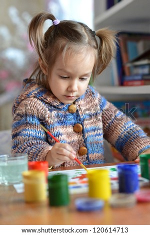beautiful baby draws paint in the room