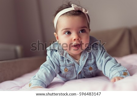 Beautiful baby girl crawling and rolling over in bed #596483147