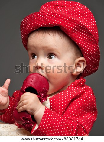 Beautiful baby girl dressed in a red dress eating her own delicious red shoe while looking very surprised