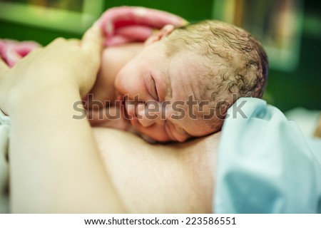 Beautiful baby girl few minutes after the birth lying on her mother, skin to skin contact
