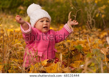 Beautiful baby girl in white hat and pink jacket crying sitting in autumn maple leaves against autumn nature