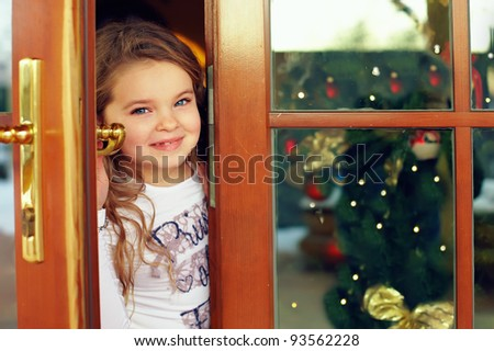 beautiful baby girl looking out from door. christmas portrait