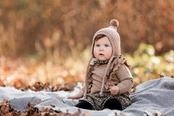 Beautiful baby girl sitting on the plaid. Child outdoor. Baby at picnic in autumn park on sunny day. Pretty little girl.