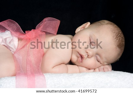 Beautiful baby girl with a pink ribbon tied around her