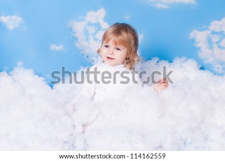 Beautiful baby girl with angel wings in white clothes posing on a background of the sky with clouds - decorated in the style of a little angel in the clouds. A series of photos in my portfolio.
