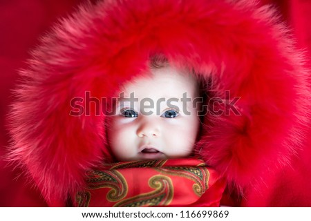 Beautiful baby girl with big blue eyes wearing a red jacket with fur hood