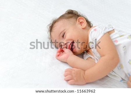 Beautiful Baby giving Laughters in the bed . - stock photo
