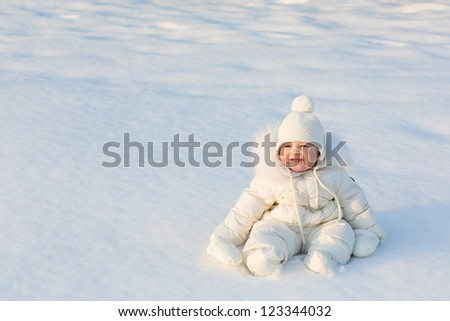 Beautiful baby in a white snow suit sitting on fresh snow on a sunny winter day