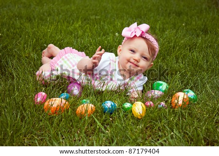 Beautiful baby laying in grass with an assortment of colored Easter eggs