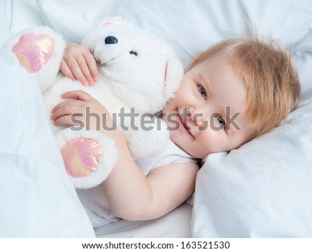 beautiful baby lying in white bed and holding a teddy bear toy