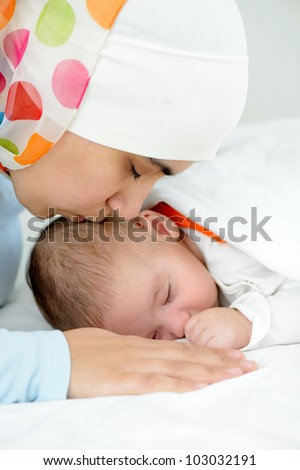 Beautiful baby of two months old in his muslim mothers hands.