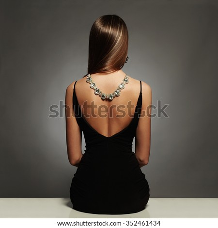 beautiful back of young woman in a black sexy dress.luxury.beauty brunette sitting girl Girl with a necklace on her back.Elegant fashion glamor photo