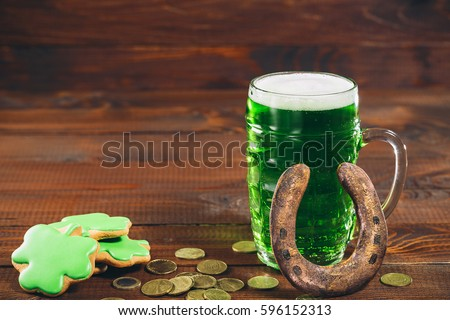 Beautiful background for St. Patrick's day with a glass of green beer, gold coins and a horseshoe on a wooden table. Free space.
