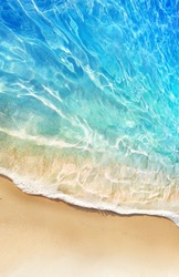 Beautiful background image tropical beach stretch of light sand, white breakers foam and amazingly clear water. Turquoise, blue, greenish shades of water and play of sunlight.