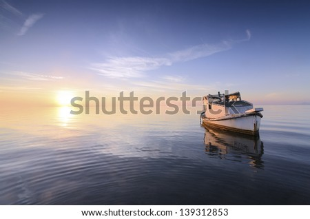 Beautiful background of sky and sea at sunrise with a little old boat abandoned in the Mar Menor, Spain