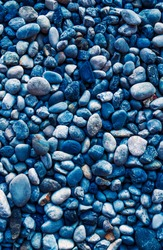 Beautiful background of smooth round pebbles sea, top view, adjusted colour to dark blue tone. Vertical image background texture of pebbles, space for text and design.
