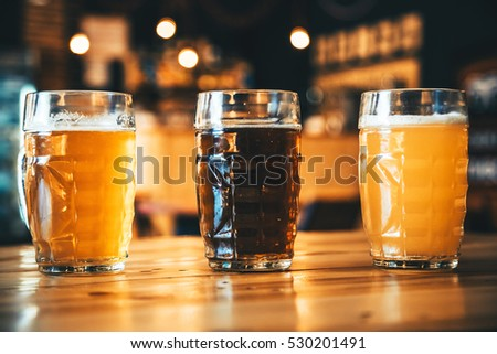 Beautiful background of the Oktoberfest. Glasses of cold fresh white, light and dark beer on the wooden bar counter in the pub. Assorted alcohol in a Flight Ready for Tasting.