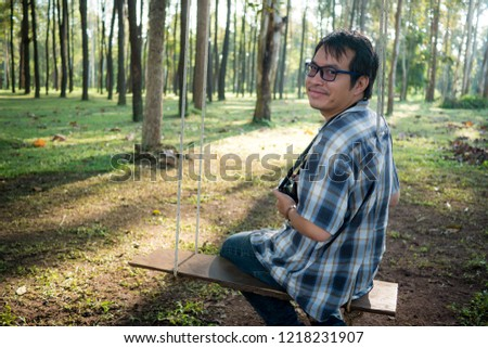 beautiful background, The man sit on swings to take pictures in the morning. The sun is shining down. Good atmosphere at the pine forest at Thailand.