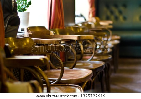 Beautiful background, view of the interior, public room, cafe, bar, reception, lobby in the old style, retro and vintage style, with wooden in the old style, retro style and vintage chairs in a row.