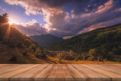 Beautiful background with sunset over mountains and empty wooden table in nature outdoor. Natural template landscape