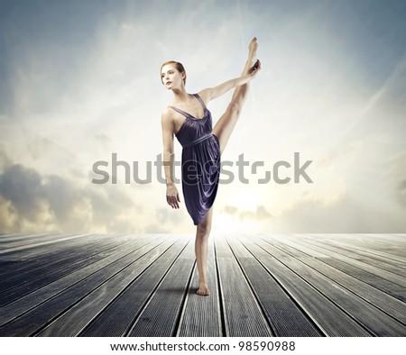 Beautiful ballerina dancing on a wood floor
