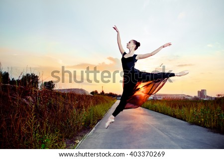 Beautiful ballerina in black skirt and leotard on street road. Focus on the dancer. #403370269