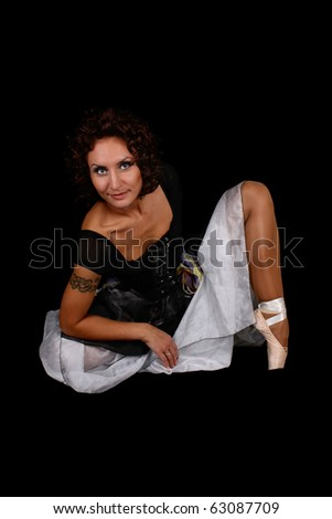 beautiful ballerina in dress sitting over black background