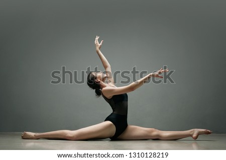 Beautiful ballet dancer doing splits stretching legs, raised arms in effortless pose on stage, indoors studio. Elegant performer, conceptual flexibility, power, visual arts discipline, physical work.