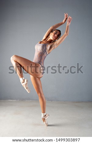 Beautiful ballet dancer in elegant pose on point shoes, harmony, conceptual off balance equilibrium, flexibility on stage indoors. Artistic discipline female shape, beauty body work, fitness lifestyle