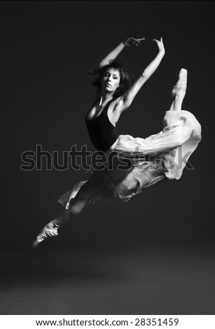 Beautiful ballet dancer in striking flying pose.
