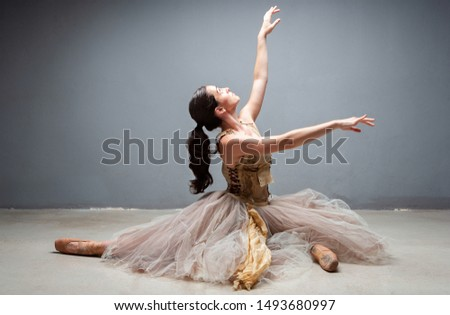 Beautiful ballet dancer on floor with tutu and point shoes stretching legs splits, romantic expression, conceptual, flexibility on stage indoors. Artistic female performer beauty body work, lifestyle.
