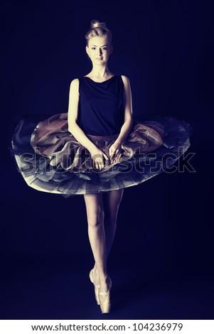 Beautiful ballet dancer posing at studio.