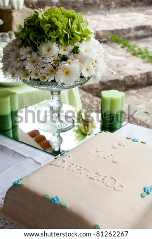 beautiful baptism or christening cake with a gorgeous flowers arrangement and candles (all in green colours)
