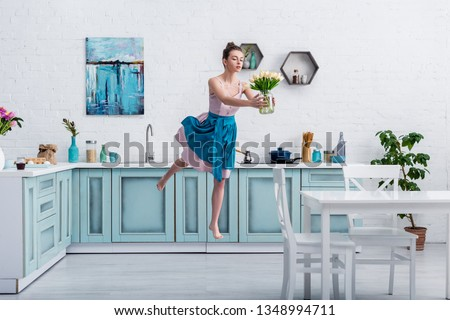 beautiful barefoot girl in elegant dress and apron flying in air with bouquet of tulips in glass jar in kitchen