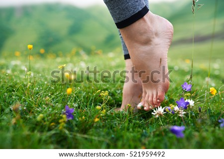 beautiful barefoot girl's legs in the cool morning dew on the grass.