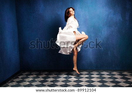 beautiful barefoot woman in white dress levitate in room