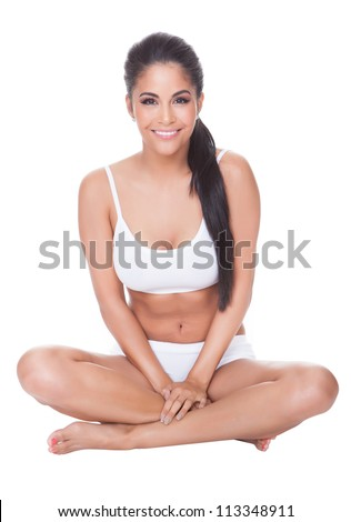 Beautiful barefoot woman sitting on the floor with her long shapely legs crossed in front of her wearing her lingerie