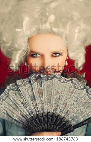 Beautiful Baroque Woman Portrait with Wig and Fan - Baroque style portrait of a young beautiful woman behind a hand fan