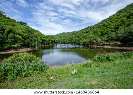 beautiful barrier lake waters inside green valley near surrounded by green trees and forest covering mountains and hills under blue sky, at Aug Kep Nam Ban Thai Prachan in Thailand #1468436864