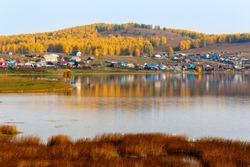 beautiful Bashkir village starobayramgulovo located among the Ural mountains on the shore of the lake Aushkul on an autumn sunny day.