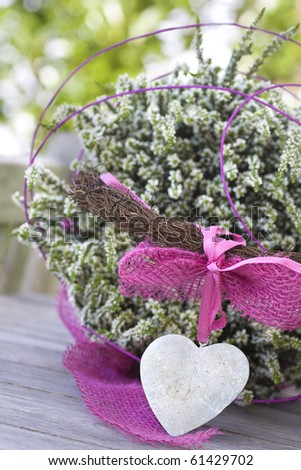 Beautiful basket with a stone heart and heather on a table