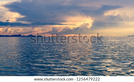 Beautiful beach blue sunset with big rain clouds and golden light sky  background #1256479222