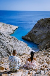 Beautiful beach called Seitan limania on Crete, Greece Europe, couple sitting on cliff looking over ocean, men and woman mid age by ocean