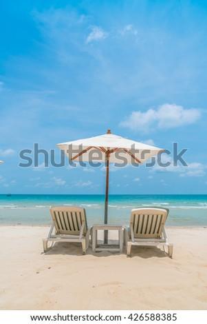 Beautiful beach chairs with umbrella on tropical white sand beach #426588385