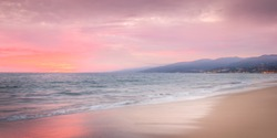 Beautiful beach destination with mountains in background during sunset with fiery pink sky