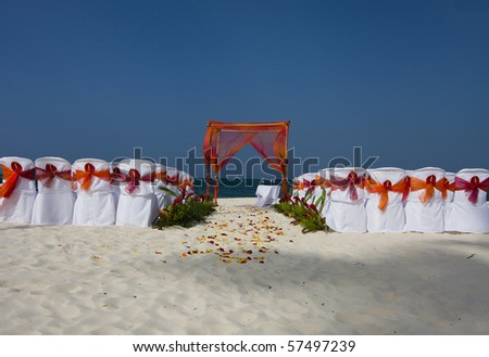 Beautiful beach scene set for a wedding ceremony with chairs, arbor, and flowers