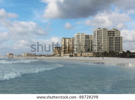 Beautiful beach scene with high rise beach front hotels in the distance.