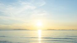 Beautiful beach sunrise with blue sea and golden light sky  cloud background