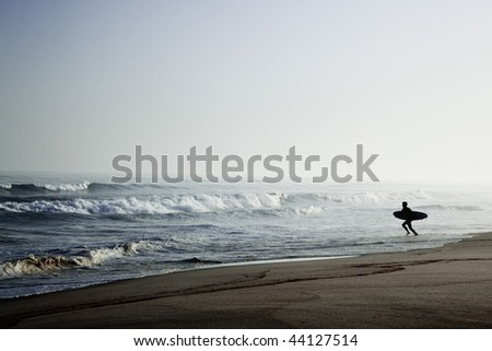 Beautiful beach with a surfer going to the waves early by the morning